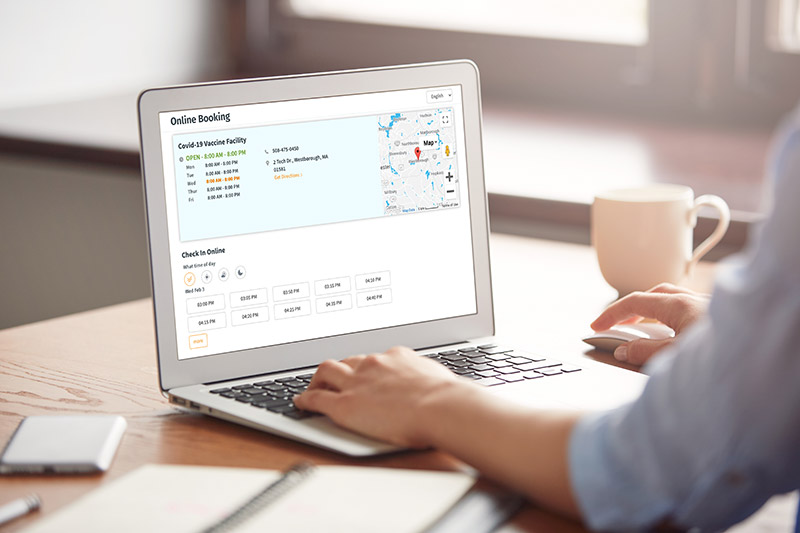 Man on laptop using healow online booking feature for Vaccine scheduling Graphic